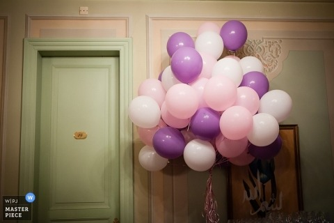 Istanbul wedding photographer gets a shot of the pink and purple balloons outside of the bridal suite