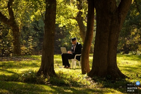 San Francisco wedding photographer captured this photo of the DJ working on his laptop in the middle of a sunny forest before the ceremony
