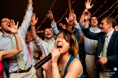 Le photographe de mariage de Providence a capturé cette photo amusante d'un invité au mariage chantant dans un micro tout en l'entourant de clients acclamant leurs mains en l'air