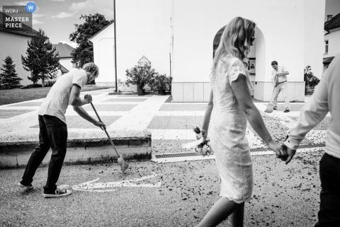 El fotógrafo de bodas de Liubliana toma una fotografía del equipo de limpieza limpiando los pétalos de rosa después de la ceremonia