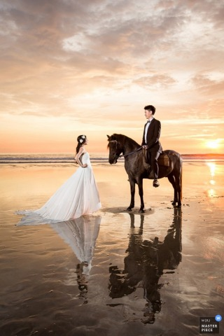 Bali wedding photographer created this portrait of a groom riding a horse while his bride stands nearby on a beach at sunset