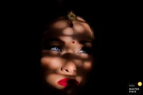 Goa-huwelijksfotograaf heeft dit beeld van de bruid en haar levendige blauwe ogen vastgelegd terwijl haar gezicht is bedekt met schaduwen