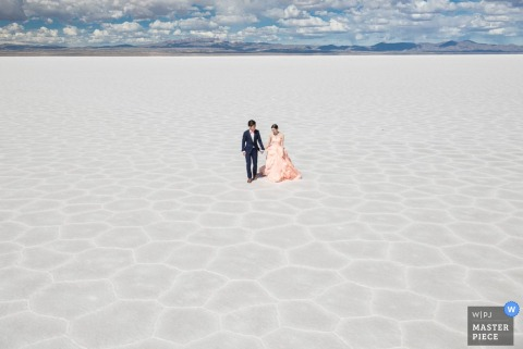 Lima wedding photographer created this portrait of a bride and groom holding hands in the wide open desert