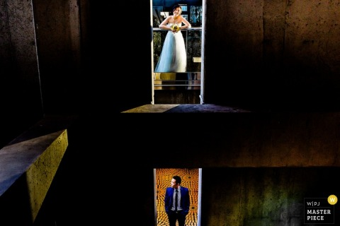 San Francisco wedding photographer created this unique portrait of the bride and groom standing on different levels of a stone warehouse