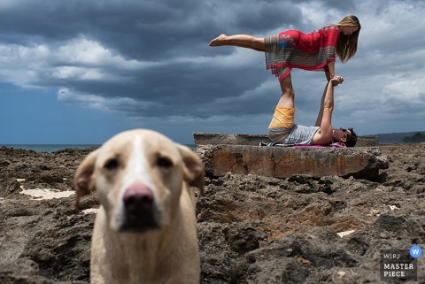 Lake Tahoe wedding photographer captured this portrait of a couple doing yoga on a rocky beach while their dog stays close by