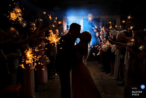 Jacksonville wedding photographer captured the silhouettes of the bride and groom kissing against the light of sparklers being held by wedding guests