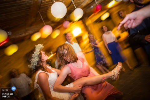 Florence wedding photographer captured this image of a floral crowned bride and her bridesmaid dancing on the dance floor