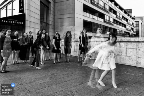 Île-de-France wedding photographer captured this photo of a bride about to toss the bouquet at the wedding reception