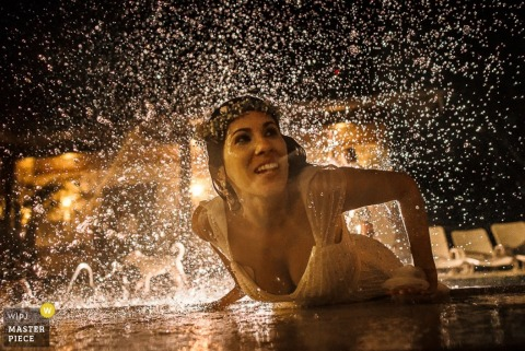 São Paulo wedding photographer captured this portrait of a bride playing in a pool still wearing her wedding dress
