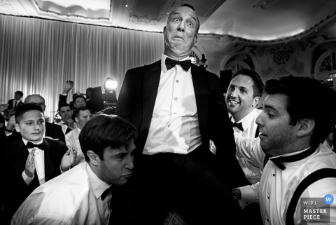 Devon wedding photographer captured this humorous photo of an uncertain man being hoisted into the air by his groomsmen