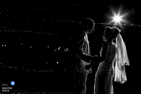 Toronto wedding photographer captured this black and white image of the bride and groom standing high above the city lights below