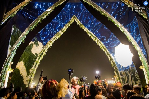 De huwelijksfotograaf van Montpellier heeft deze foto van een nachtelijke ontvangst gemaakt omdat verschillende camera's de bruid en bruidegom vastleggen terwijl ze zich bevinden onder verlichte, blauwe bogen