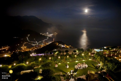 Siena wedding photographer captured this aerial shot of an outdoor garden reception as the moon reflects on the ocean in the distance