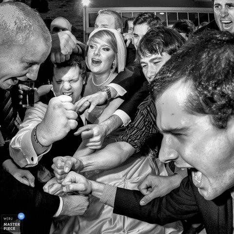 Baton Rouge wedding photographer captured this black and white photo of an exuberant wedding party fist bump at the wedding reception