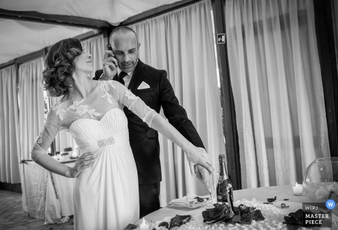 Florence wedding photographer captured this black and white photo of the groom making a call on his cellphone while his bride watches with her hands on her hips