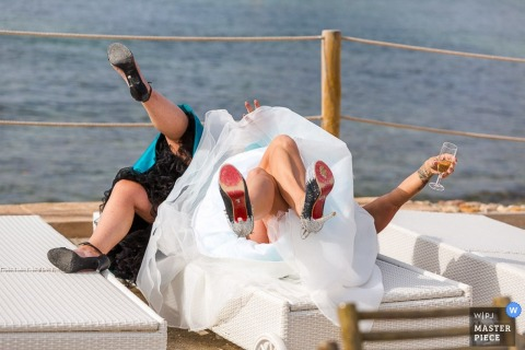 Malta wedding photographer captured this photo of a bride and bridesmaid laying back on waterfront bench while holding a glass of champagne