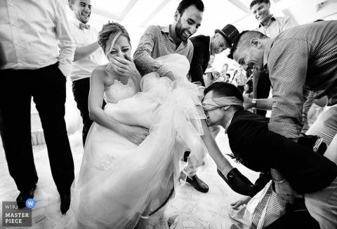 Der Hochzeitsfotograf von Lecce hat dieses Schwarzweißfoto eines Bräutigams mit verbundenen Augen aufgenommen, der das Strumpfband mit den Zähnen von seiner kichernden Braut entfernt