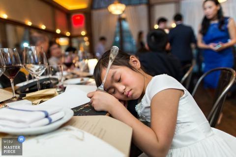 De bruidsfotograaf van Brooklyn ving dit kleine meisje, dat het zat was om te wachten op haar eten bij de receptie en in slaap viel op de tafel, vork in de hand