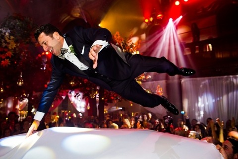 Wedding Reportage Photographer David Pullum of London shot this groom flying on the dance floor at his reception.