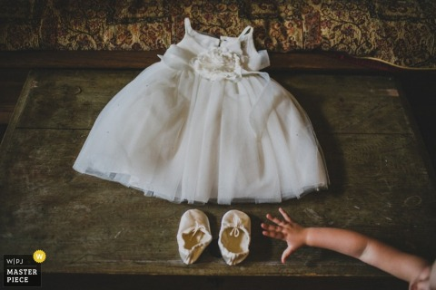New South Wales wedding photographer captured this detail image of a tiny flower girl dress and slippers waiting for it's occupant