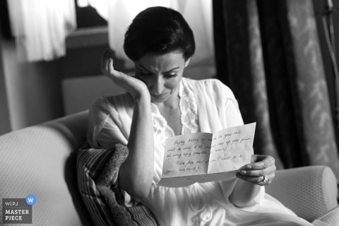 Rome wedding photographer captured this black and white image of a bride wiping her eyes as she reads a letter before her ceremony