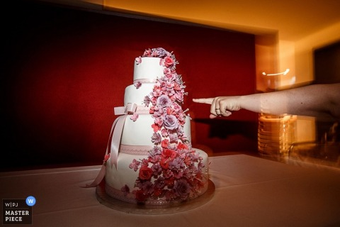 Lower Saxony wedding photographer captured this detail image of a white cake with pink and red flowers as a finger points out a particularly tasty detail to a wedding guest off camera