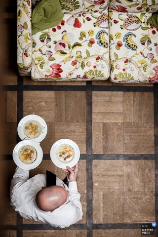 Lower Saxony wedding photographer captured this overhead photo of a caterer walking through the reception carrying bowls of soup