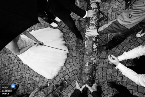 Lower Saxony wedding photographer captured this black and white photo of a bride and groom participating in an old German custom of sawing a log together to surpass their first obstacle as husband and wife