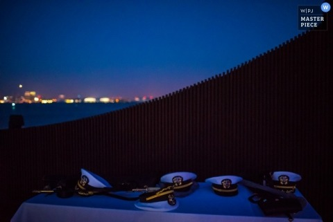 San Diego wedding photographer captured this detail image of a table full of servicemen hats sitting in front of the city skyline