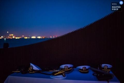 De huwelijksfotograaf van San Diego legde dit detailbeeld vast van een tafel vol militairenhoeden die voor de skyline van de stad zaten