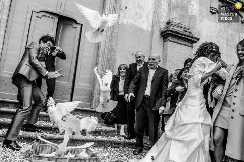 Lecco-trouwfotograaf heeft dit humoristische beeld vastgelegd van de bruid en bruidegom die duiken bij duiven terwijl ze na de ceremonie naar binnen schieten