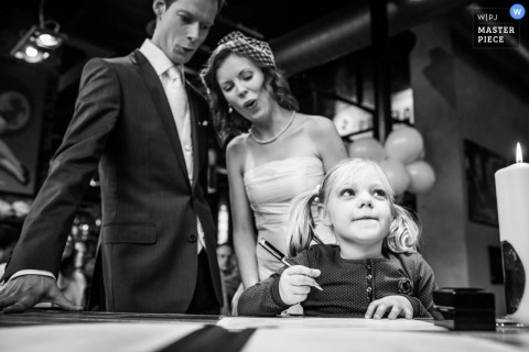 Overijssel wedding photographer captured this black and white photo of the bride and groom with a little girl at the marriage certificate signing