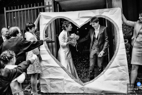 Turin wedding photographer captured this photo of the bride and groom standing in the cut out of a large paper heart after their ceremony