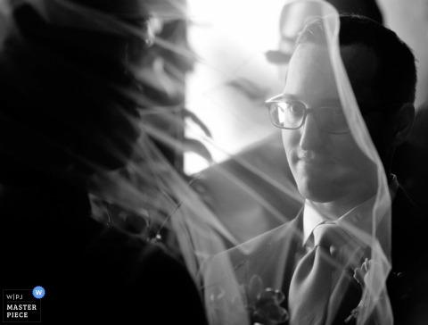 Le photographe de mariage de Worcester a capturé cette photo en noir et blanc d'un époux admirant sa fiancée à travers le voile de son voile