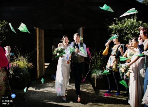 Der Londoner Hochzeitsfotograf hat dieses Foto der Braut und des Bräutigams aufgenommen, die die Zeremonie inmitten eines Sturms von Papierflugzeugen verlassen