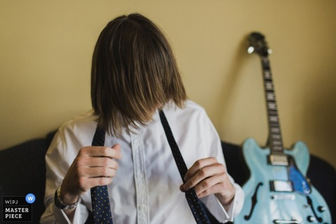 New South Wales wedding photographer captured this image of a groom tying his tie as his favorite blue guitar sits behind him