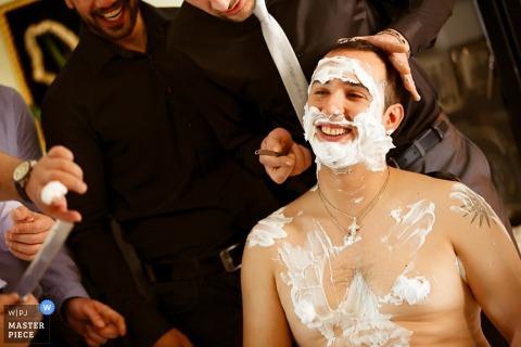 De het huwelijksfotograaf van Thessaloniki ving dit beeld van een glimlachende bruidegom die een scheerbeurt krijgen vóór het huwelijk