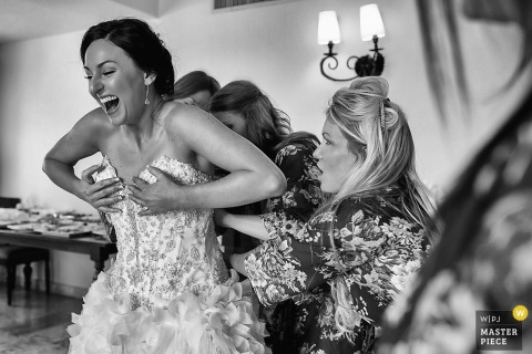 Playa del Carmen wedding photographer captured this black and white photo of a bride laughing as they work to put on her dress while her bridesmaid is flabbergasted on what to do next