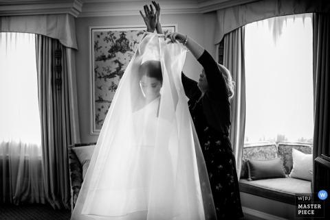Der Devon-Hochzeitsfotograf hat dieses Schwarz-Weiß-Bild der Braut aufgenommen, die beim Anziehen des letzten Teils ihres Kleides Hilfe bekommt