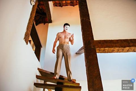 Le photographe de mariage de Ljubljana capture ce marié avec un masque facial au sommet d'un escalier en bois en colimaçon