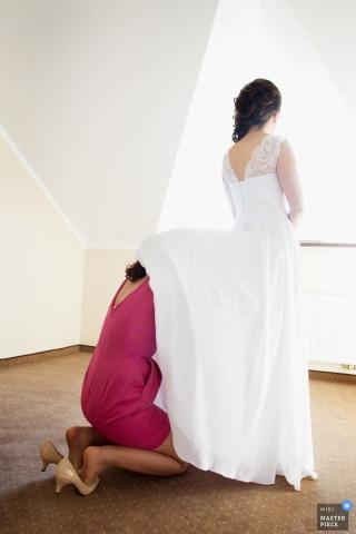 Krakow wedding photographer captured this photo of a bride getting assistance with her dress from a bridesmaid