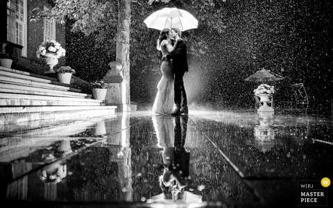 A bride and groom kiss under an umbrella as they are reflected on the wet ground in this black and white wedding photo composed by a Netherlands documentary photographer.
