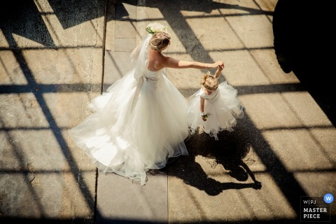 The bride dances with a little girl in this wedding photo captured by an award-winning Netherlands photographer.