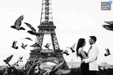 Brussels wedding photographer captured this black and white photo of the bride and groom embracing in front of the Eiffel Tower as pigeons fly around them
