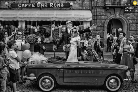 The bride and groom stand up in their car as guests send them off in this black and white photo by a Piedmont wedding photographer.