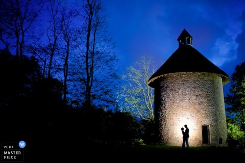 Jersey wedding photographer captured the silhouettes of the bride and groom embracing against a stone structure at night