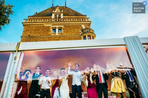 The wedding party stands together under the reception tent in this portrait by a Slovenia wedding photographer.