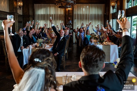 The bride, groom, and guests all raise their glasses in a toast in this wedding photo by a documentary-style Lake Tahoe, CA photographer.