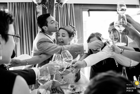 The bride, groom, and guests all reach over each other to toast everyone in this black and white photo by a Nantes wedding photographer.