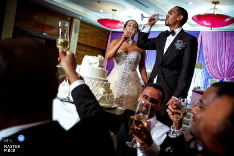 Toronto wedding photographer captured this photo of the bride and groom toasting champagne before cutting their cake